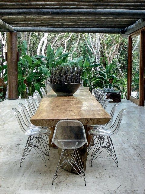 a gorgeous rough wood table with legs and lucite chairs look natural and modern