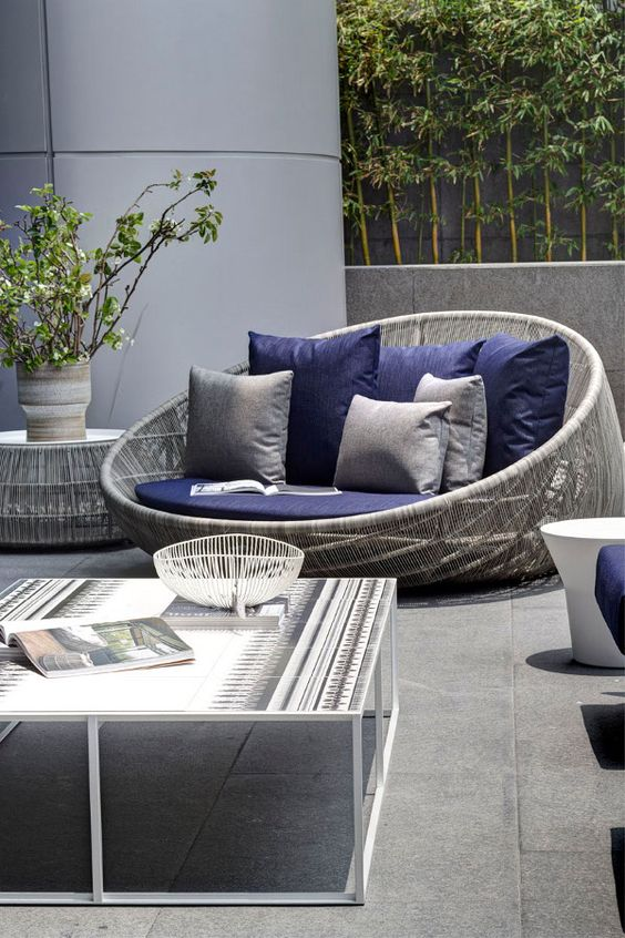 grey wicker love seat with navy cushions look great together