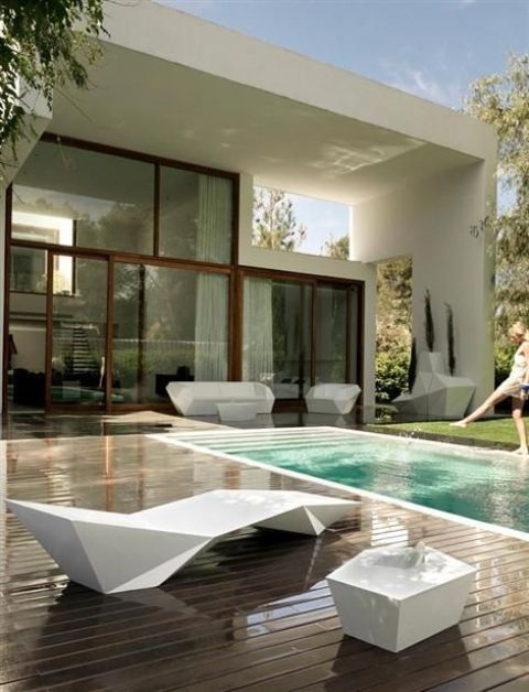 a modern white sculptural lounger and a table for a pool area