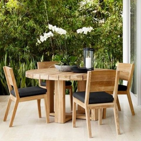 light-colored round wooden table with matching chairs and black upholstery