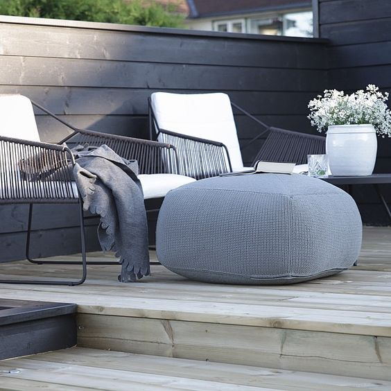 dark wicker furniture and a grey fabric ottoman look very laconic